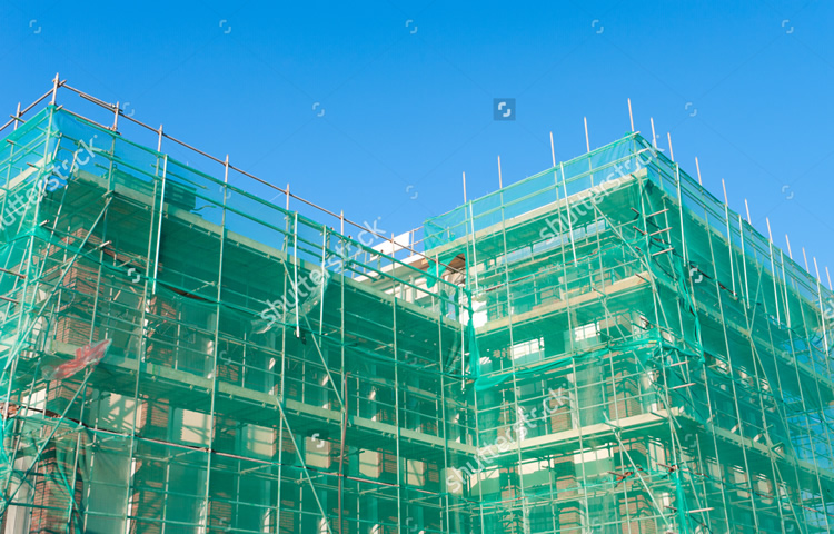 stock-photo-building-under-construction-wrapped-in-a-green-net-for-safety-97852178